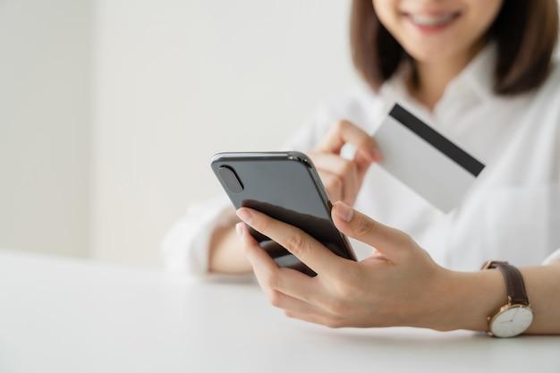 Frau, die kreditkarte und zahlung online auf smartphone hält.