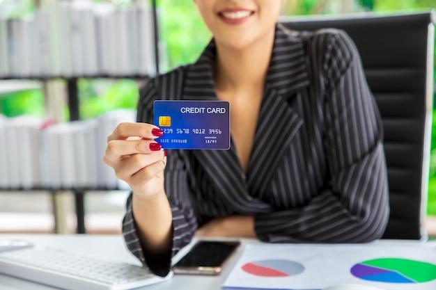 Frau, die kreditkarte verwendet, um die rechnung zu bezahlen.