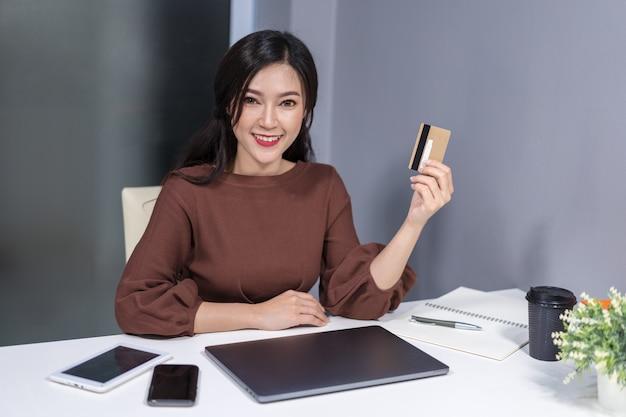 Frau, die kreditkarte zum on-line-einkaufen verwendet