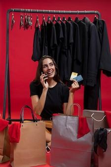 Frau, die kreditkarten bei der unterhaltung am telefon hält