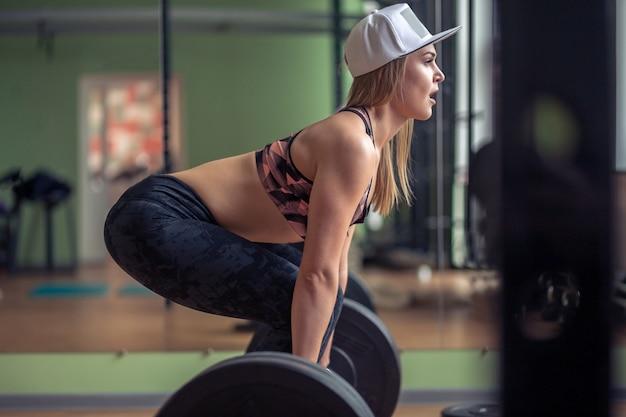 Frau, die kreuzhebenübung mit gewichtsstange durchführt. zuversichtlich junge frau, die gewichtheben training im fitnessstudio macht