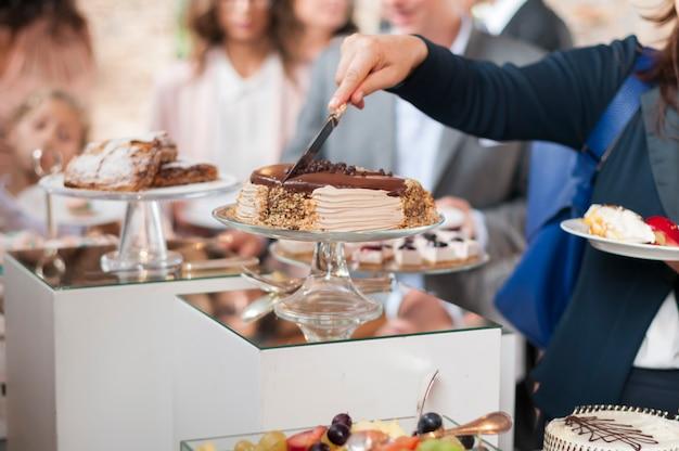 Frau, die kuchen auf einem catering schneidet