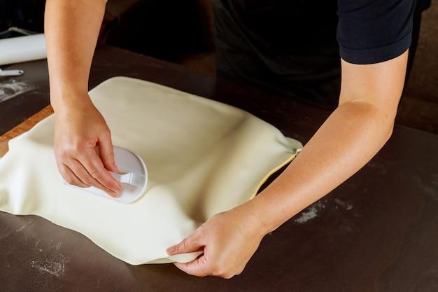 Frau, die kuchen mit fondant für partei macht. technik des bäckers.