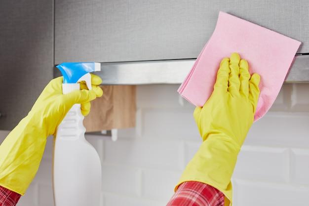 Frau, die küche putzt. junge frau, die küchenhaube mit spray wäscht. nahansicht