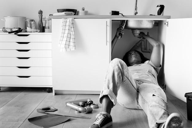 Frau, die küchenspüle repariert