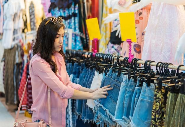 Frau, die kurze hosen im einkaufsspeicher wählt und kauft