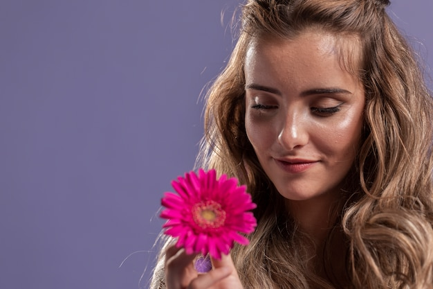 Frau, die lächelt, während sie eine chrysantheme mit kopienraum hält