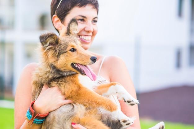 Frau, die lächelt, während sie ihren hund hält, der die zunge herausstreckt. frau mit haustier im garten entspannen. frohe frau, die ihren hund draußen trägt