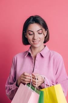 Frau, die lässigen pullover auf hintergrund glücklich genießt das einkaufen hält bunte taschen