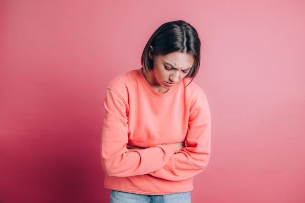 Frau, die lässigen pullover auf hintergrund leidet, der bauchschmerzen mit schmerzhafter grimasse leidet, plötzliche zeitkrämpfe, gynäkologisches konzept fühlt