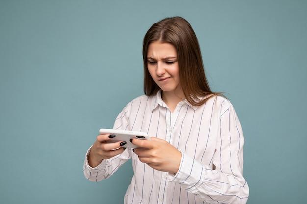 Frau, die lässiges weißes hemd isoliert über blauem hintergrundwand hält smartphone hält und online-spiele spielt