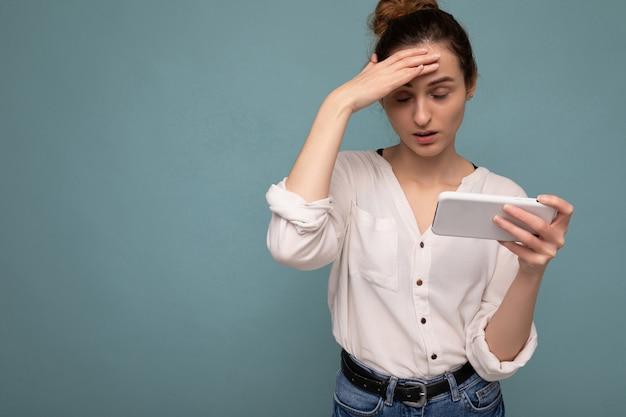 Frau, die lässiges weißes hemd trägt und lokalisiert über blauem hintergrundwand hält und telefon verwendet
