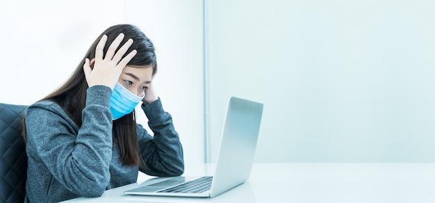 Frau, die laptop auf schreibtisch mit kopfschmerzen tragenden maske zum schutz von covid-19 verwendet
