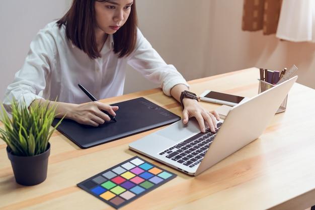 Frau, die laptop auf tabelle im büroraum, für grafikanzeigenmontage verwendet.