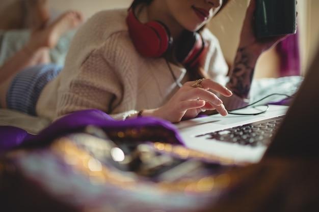 Frau, die laptop beim kaffee auf bett verwendet