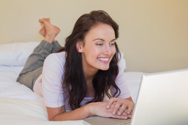 Frau, die laptop beim lügen im bett verwendet