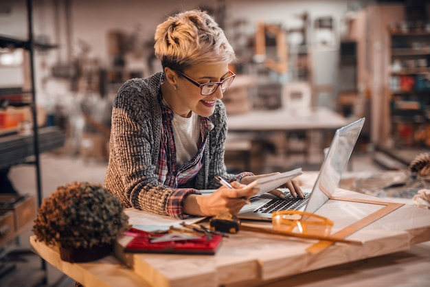 Frau, die laptop beim stehen in der tischlerwerkstatt verwendet
