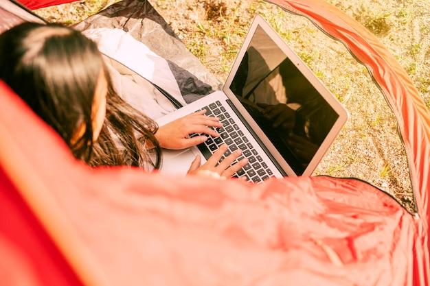 Frau, die laptop beim stillstehen beim kampieren verwendet