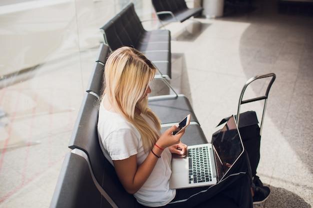 Frau, die laptop-computer am flughafenterminal sitzt mit gepäckkoffer und rucksack für reisen im urlaubssommer entspannender wartender flugtransport sitzt.