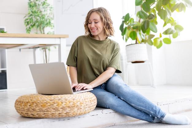 Frau, die laptop-computer beim sitzen des fußbodens zu hause verwendet. freiberufliche frau, die von zu hause aus arbeitet fernstudentin, die sich entspannt und unterricht auf videokonferenzen beobachtet
