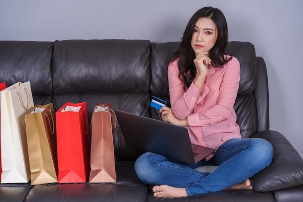 Frau, die laptop-computer für das on-line-einkaufen mit kreditkarte im wohnzimmer denkt und verwendet