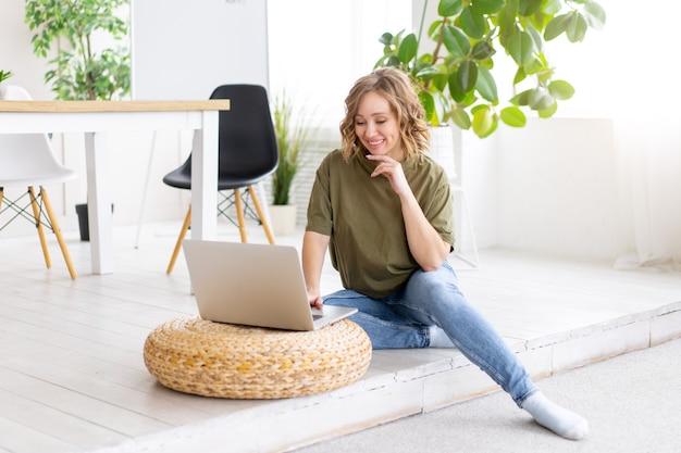 Frau, die laptop-computer verwendet, während boden zu hause innen sitzt. freiberufliche frau, die von zu hause aus arbeitet