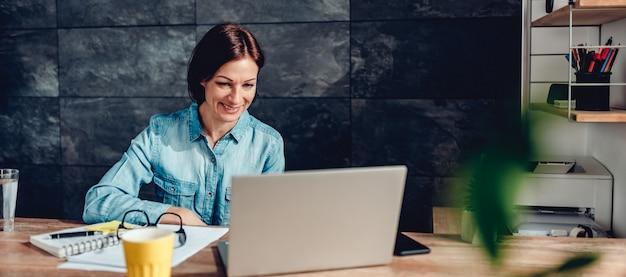 Frau, die laptop im büro und im lächeln verwendet