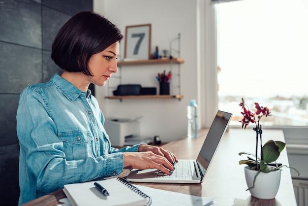 Frau, die laptop im büro verwendet