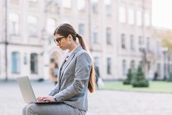 Frau, die Laptop in der Stadt verwendet