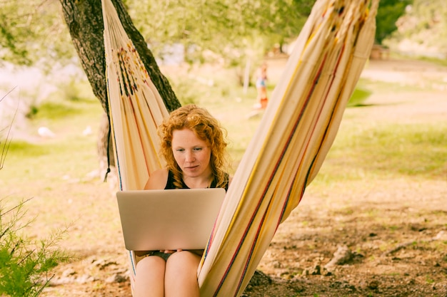 Frau, die laptop in gestreifter hängematte verwendet