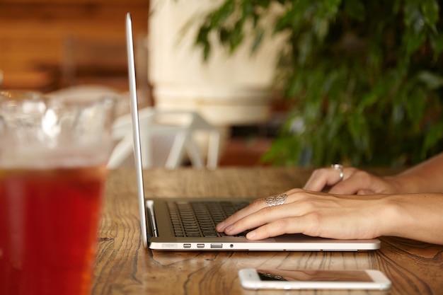 Frau, die laptop-tastatur tippt