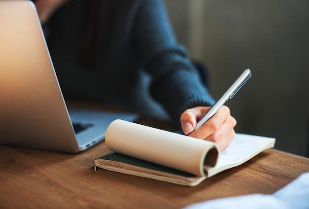Frau, die laptop-technologie-schreibens-arbeitsplatz-konzept bearbeitet