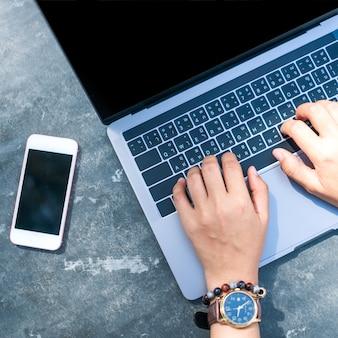 Frau, die laptop und smartphone verwendet, um studie im urlaub cady am strand hintergrund zu arbeiten. business-, finanz-, trade stock maket- und social network-konzept.