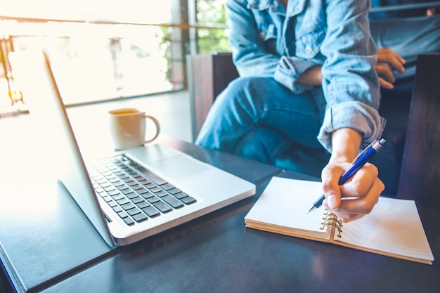 Frau, die laptop verwendet und in notizblock schreibt.