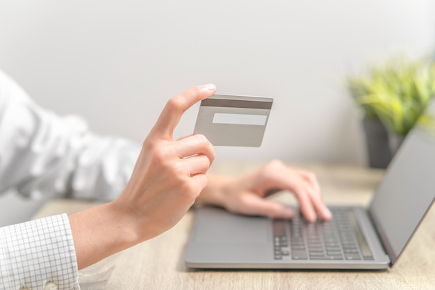 Frau, die laptop verwendet und kreditkarte in den händen hält.