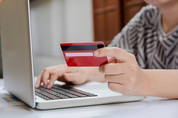 Frau, die laptop verwendet und kreditkarte mit dem on-line-einkaufen oder internetbanking online hält.