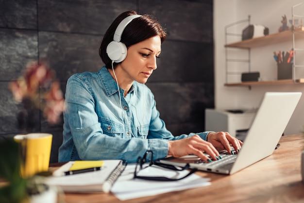 Frau, die laptop verwendet und musik auf kopfhörer hört
