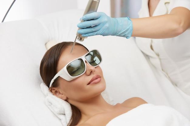 Frau, die lasertherapie für stirn trägt, die schutzbrille trägt