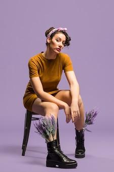 Frau, die lavendelblumen in den stiefeln sitzt und hat