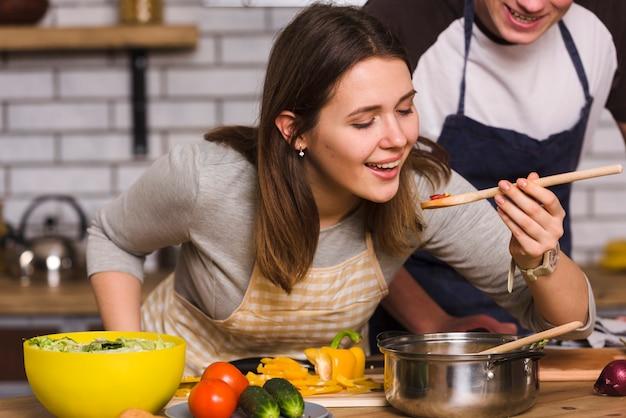 Frau, die lebensmittel beim kochen mit freund schmeckt