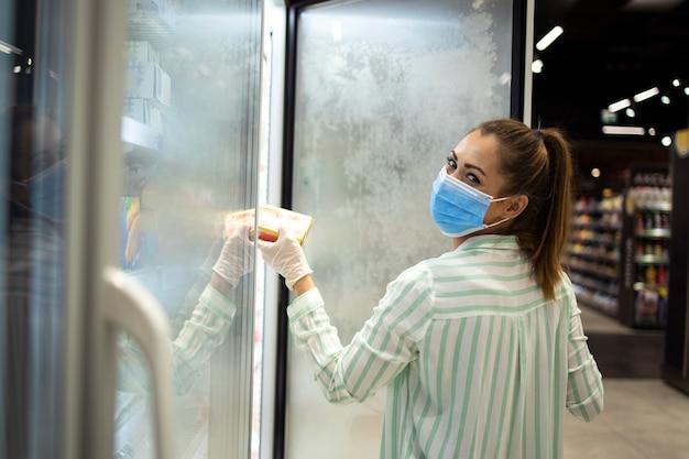 Frau, die lebensmittel im supermarkt kauft und sich gegen hoch ansteckende koronavirus-pandemie schützt