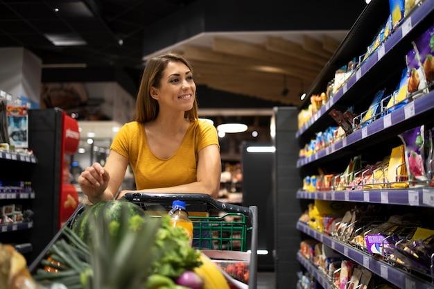 Frau, die lebensmittel im supermarkt kauft
