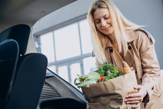 Frau, die lebensmittel in einkaufstasche in ihr auto steckt