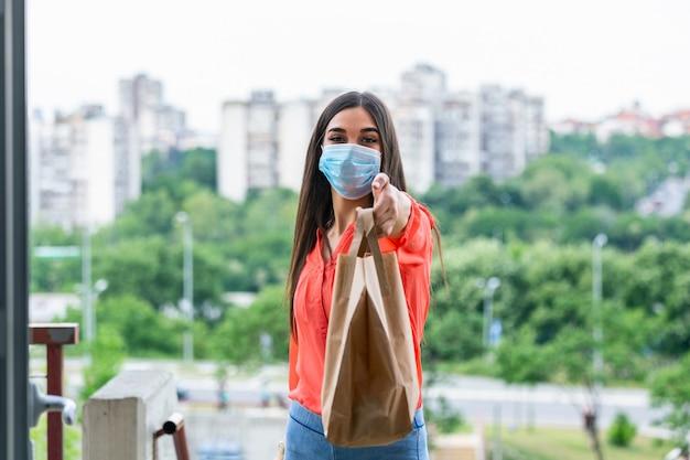 Frau, die lebensmittel in papiertüte während covid 19 coronavirus ausbruch liefert. feme freiwilliger hält lebensmittel in der veranda des hauses