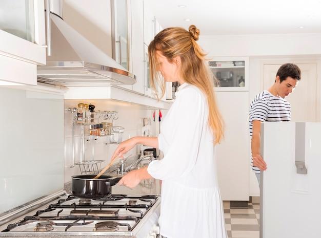 Frau, die lebensmittel während ihr ehemann schaut im kühlschrank zubereitet