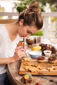 Frau, die lebkuchen mit bürste verziert