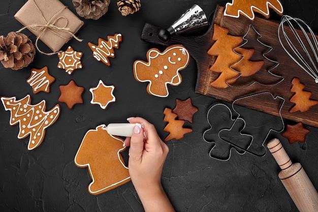 Frau, die lebkuchen-weihnachtsplätzchen mit puderzucker auf dunklem hintergrund verziert. urlaub, feiern und kochkonzept. weihnachtsvorbereitungen konzept. draufsicht mit kopienraum.