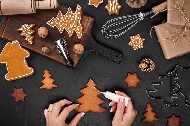 Frau, die lebkuchen-weihnachtsplätzchen mit puderzucker-weihnachtszubereitung-konzept oben v...