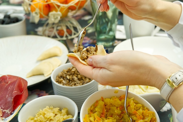 Frau, die leckere knödel kocht, nahaufnahme. diy hausgemachte knödel mit verschiedenen füllungen. kartoffelknödel