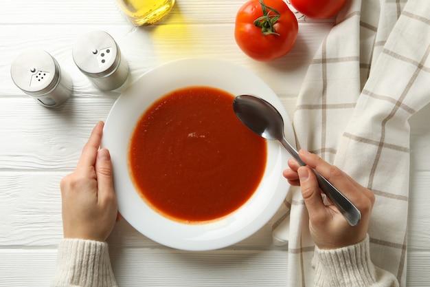 Frau, die leckere tomatensuppe auf weißem holz isst